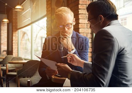 Pensive business people analyzing chart in their hands