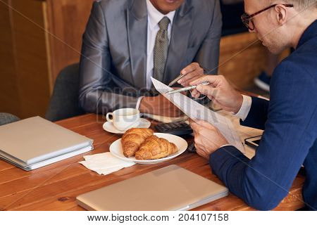 Cropped image of colleagues analyzing financial report together