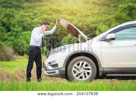 Full length of worried businessman by broken down car at countryside man besides he broken car talking on the cell phone