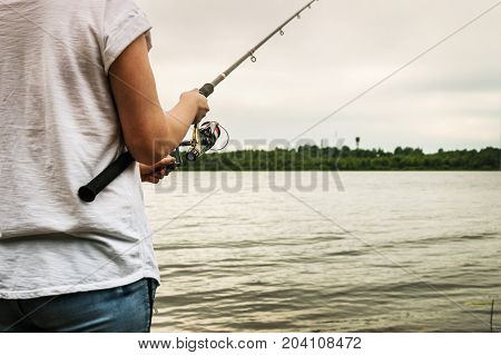hands holding a fishing rod and twist the handle of the fishing reel. Shallow depth of field, soft focus
