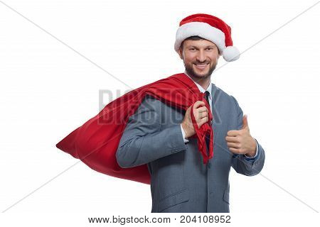Portrait of positive santa claus in gray suite, red cap and full bag over shoulder, smiling and showing super. Happy santa preparing presents looking at camera, gesturing by finger. Christmas concept.