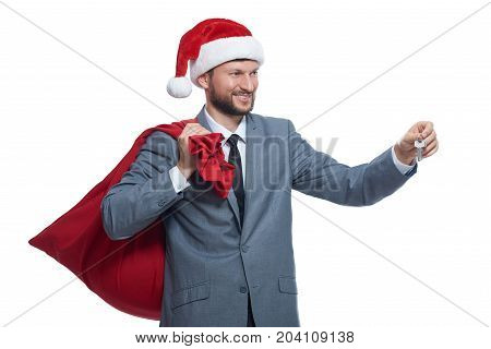 Santa clause in gray suite, red cap holding full bag over shoulder, smiling, looking away, giving key. Santa giving key rich present, flat, house or car. New year concept. Isolate on white.