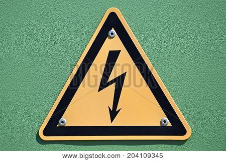 Electricity sign danger on a green background