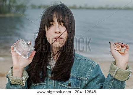 Cute woman with perfume bottle at nature background