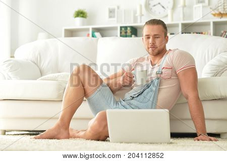 Handsome young man sitting on white couch with laptop
