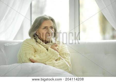 Portrait of ill senior woman lying on white couch