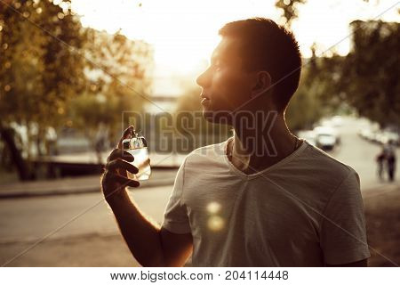 Male perfume. man holding perfume at sunset outdoors