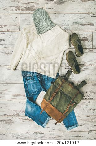 Flat-lay of Fall lady' s clothes outfit. Ecru colored knitted woolen sweater with braids, blue denim jeans, haki suede oxford boots, backpack, cap over parquet background, top view. Trendy Autumn look
