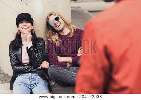 loughing young couple talking with friend outdoors