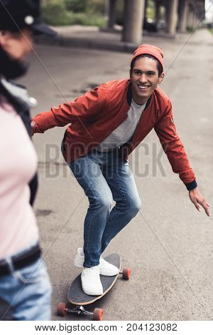 handsome happy man riding to girlfriend on skateboard