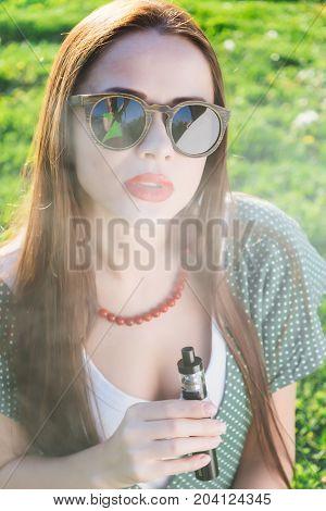 Happy fashion smiling Woman in sunglasses smoking vape on street,smoker