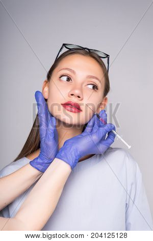 Hands doctor to prick a girl hyaluronic acid in the face.