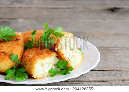 Stuffed vegetable cutlets on a serving plate and a vintage wooden background. Cutlets made from cauliflower and potatoes and stuffed with hard boiled sliced eggs. Closeup