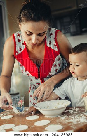 Little Boy With Mom In The Kitchen Preparing Dough