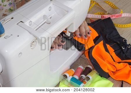 designer making a garment in her workplace. Woman tailor working on sewing machine