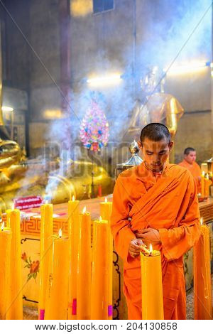 Chachoengsao Thailand - July 13 2013: Chinese Buddhist monks lighting the candles to worship golden Buddha Image in chinese shrine in Chachoengsao Thailand