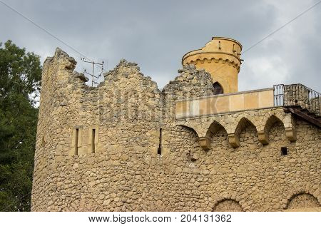 The walls of the old castle. The background is a blue sky with white clouds. The castle tower is visible in the background. Antennas for TV reception are visible on the walls.