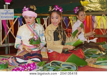 CHIANG MAI, THAILAND - NOVEMBER 12, 2008: Unidentified women wearing traditional dresses make Krathong flower bowls with banana leaves during Loi Krathong celebration at ningt in Chiang Mai, Thailand.