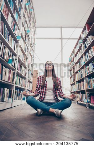 Wellness peace chill rest wisdom education campus lifestyle. Low angle shot of young calm nerdy girl practicing yoga in the lotus position on wooden floor in archive room of college library