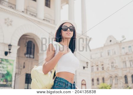 Pretty Hot Mulatto Model In Trendy Fashionable Sunglasses And White Cap On The Stroll In Town With A