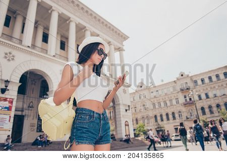 Young Lady Is Browsing On Her Pda While On Stroll Outside In The Town. She Has Bare Stomach, Amazing