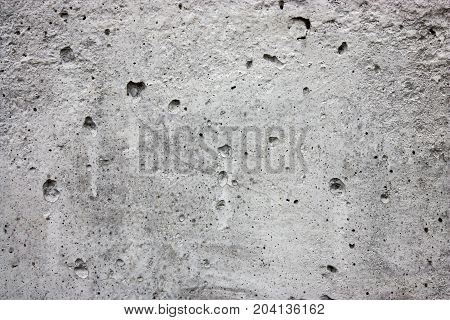 Texture of gray concrete with cracks and pores.