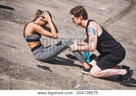 Man Helping Sportive Woman With Training