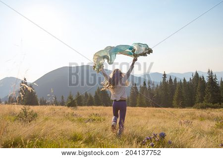 Happy Teenage Girl Runs Along The Alpine Meadow With A Waving Scarf