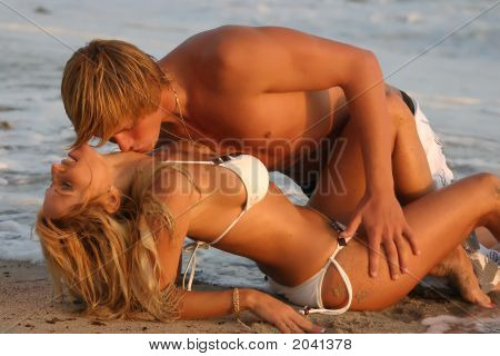 Young Couple Kisses On The Beach At Sunset