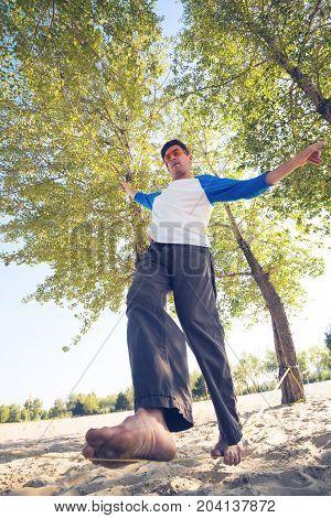Man Barefoot Is Walking On Slackline