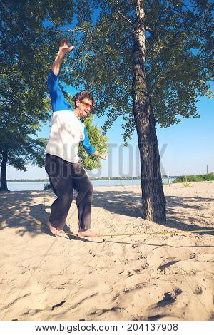 Concentrated Man, With Difficulty, Balances On Slackline