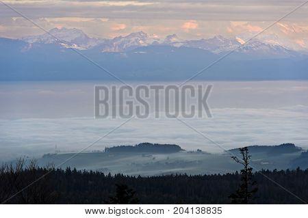 Autumn fog lingering above Lake Geneva French Alps behind Nyon Switzerland