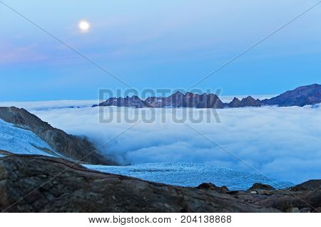 Full moon above the sea of fog over the Chamonix valley mountain range Aiguilles Rouges behind Chamonix Haute-Savoie France