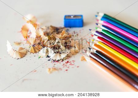 A lot of colored pencil shavings on a white background on the table
