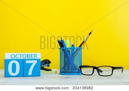 October 7th. Day 7 of month, wooden color calendar on teacher or student table, yellow background . Autumn time. Empty space for text.