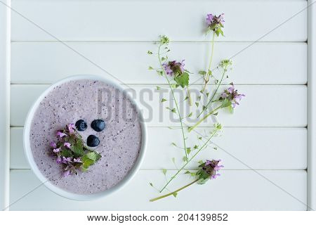 Oatmeal porridge made of oats mashed banana almond milk and berries all mixed together isolated on white wooden background with fresh thyme and shepherd's pouch