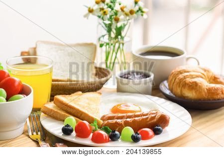 Homemade american breakfast with sunny side up fried egg toast sausage fruits vegetable strawberry jam coffee croissant and orange juice in side view. Delicious american breakfast for family. American breakfast for family.