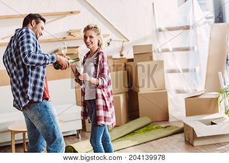happy young man pouring champagne to cheerful girlfriend in new house