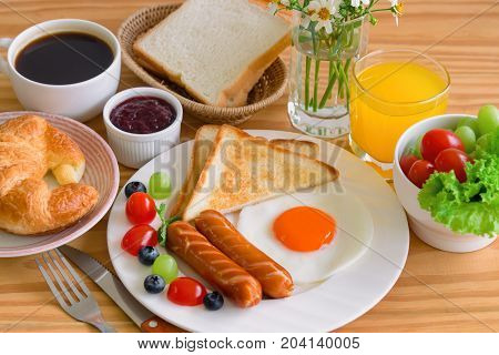 Homemade breakfast with sunny side up fried egg toast sausage fruits vegetable strawberry jam and orange juice in top view. Delicious homemade american breakfast concept for background or wallpaper. American breakfast on breakfast table.