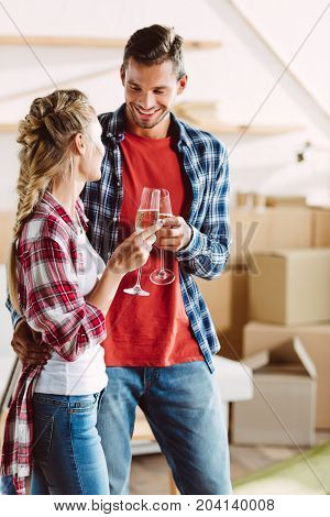 happy young couple clinking glasses of champagne and smiling each other in new house