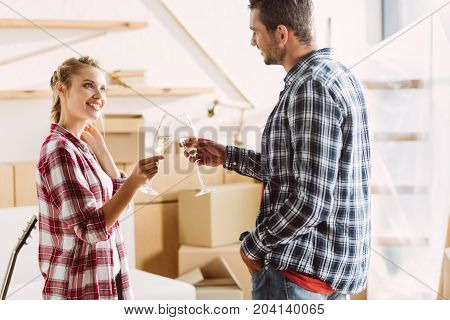 happy young couple clinking glasses of champagne and smiling each other in new apartment