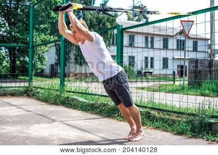 A sports person, in the fresh air is engaged in training trx, in sports clothes, in the summer in the city, wringing out. Strength and stamina motivation.