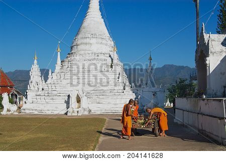 MAE HONG SON, THAILAND - NOVEMBER 16, 2008: Unidentified Buddhist monks clean territory of the Wat Phra That Doi Kong Mu temple in Mae Hong Son, Thailand.