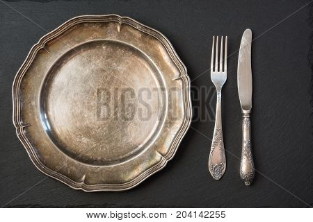 Empty vintage metal plate with silverware on black with copy space for your menu or recipe. Menu card for restaurants. Table plase setting.