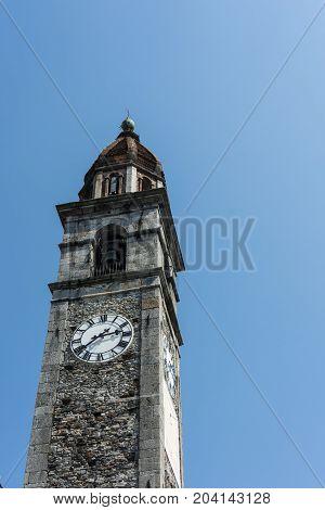 Clock tower of Chiesa Parrocchiale dei Santi Pietro e Paolo at center square in Ascona, Locarno, Switzerland wit blue sky