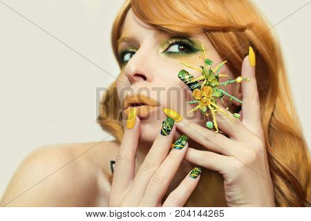 Green yellow bright fashion makeup and manicure with different shape and color and length of nails with sparkles on the girl with red hair on gray background.Nail art.
