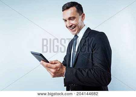 Happiness overload. Waist up shot of an excited mature man wearing a black suit grinning broadly while looking at a screen of a digital tablet over the background.
