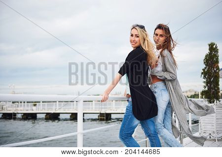 Happy young girl in stylish clothing brands on the pier near the water.