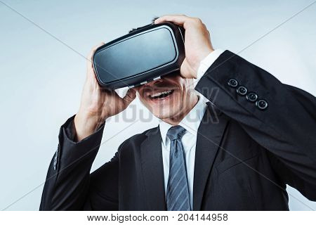 I cannot believe this. Scaled up look on a male entrepreneur trying on the latest model of a virtual reality headset and enjoying the process while standing over the background.