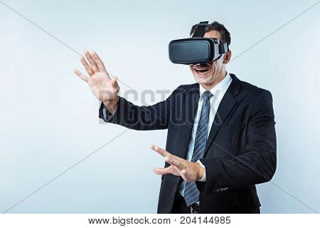 Where am I. Lost in a virtual reality office worker keeping his mouth opened while trying to find the right way over the light background.